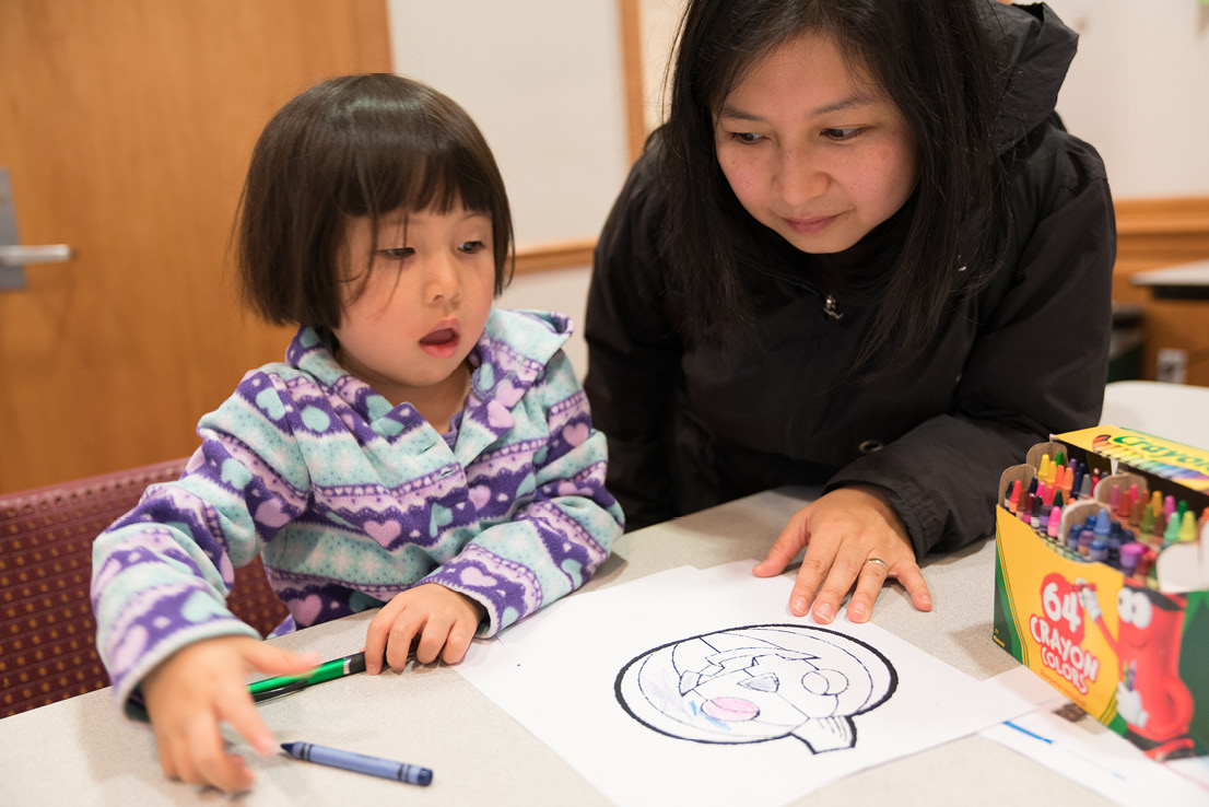 A mother and her daughter spend time at a coloring themed passport station to work on the daughter's fine motor skills.
