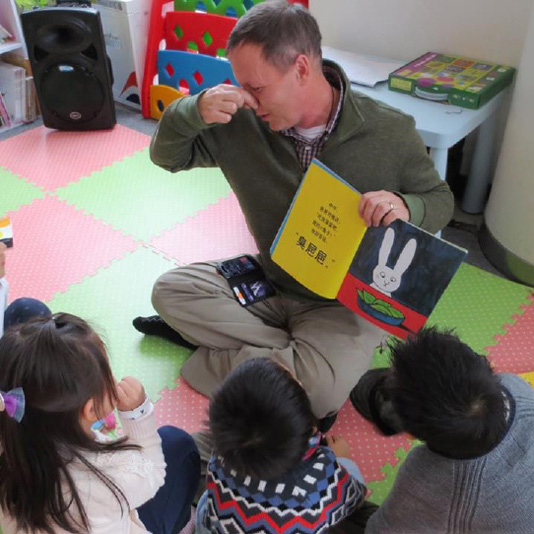 The author reads Stinky Poop to members of Li Na's Little Leaves children's library in Shanghai.