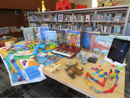 A library display of picturebook biographies, toys, and games.