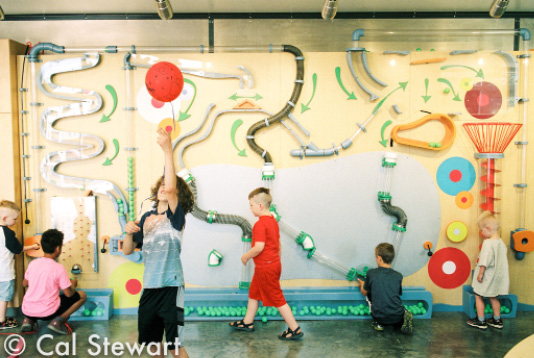 Children interact with a wall display.